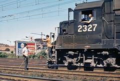 Penn Central train orders are being passed by Bob Hughes to a cab crew member of a westbound EMD GP35 locomotive # 2327, that is passing by tower SS38, along the former New Haven Railroad right-of-way  at Stamford, Connecticut, ea 1970's, Bob Hughes Photo (alcomike43) Tags: penncentral pc newhavenrailroad railroads trains stamfordconnecticut tower signalstation ss38 trainorders bobhughes engineer fireman conductor cabcrewmembers locomotives engines diesels emd gp35 2327 dieselengine diesellocomotive dieselelectriclocomotive electrification catenary insulators people employees city downtown buildings highway i95 tracks rails ties rightofway siding mainline jointedsectionrail anglebars spikes tieplates photo photograph slide color old historic vintage classic