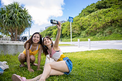 Young women taking selfie picture in resort beach (Apricot Cafe) Tags: japan asia naha carefree okinawaprefecture japaneseethnicity millennialgeneration asianandindianethnicities travel summer sky people tourism nature grass smiling outdoors photography freedom togetherness day sitting friendship fulllength relaxing happiness tourist jeans filmcamera copyspace vacations twopeople sandal enjoyment photographing lifestyles selfie sleeveless shortpants toothysmile casualclothing realpeople traveldestinations leisureactivity onlyyoungwomen women youngadult imgr32691