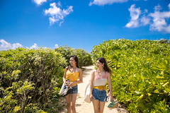 Young female friends walking on narrow path to the beach (Apricot Cafe) Tags: blue japan asia naha okinawaprefecture japaneseethnicity millennialgeneration asianandindianethnicities travel summer sky people tourism nature smiling walking outdoors photography freedom togetherness leaf women day friendship happiness tourist communication jeans walkway copyspace youngadult vacations twopeople carefree enjoyment lifestyles sleeveless shortpants casualclothing realpeople cloudsky traveldestinations leisureactivity threequarterlength greedily onlyyoungwomen drinkingbottle resuablebottle imgr32647