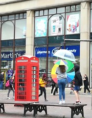 Phone box (daveandlyn1) Tags: phonebox redphonebox oldstyle k6 see bench seating teenagers youngsters umbrellas girls public passersby pralx1 p8lite2017 huaweip8 cameraphone android psdigitalcamera shops chester