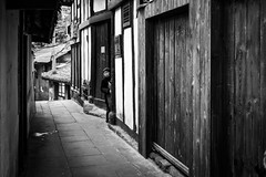 The lady from the alley (Go-tea 郭天) Tags: chongqing républiquepopulairedechine narrow alley old ancient traditional tradition history historical historic construction building wood wooder door woman lady hidden sun sunny shadow portrait pavement street urban city outside outdoor people candid bw bnw black white blackwhite blackandwhite monochrome naturallight natural light asia asian china chinese canon eos 100d 24mm prime alone lonely