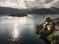 Isola di San Giulio - Orta San Giulio (Italy) (Andrea Moscato) Tags: andreamoscato italia montagna landscape light luce paesaggio sky shadow cielo clouds nature natura nuvole natural naturale view vista vivid day panorama lago lake water freshwater ombre yellow mountain island isola city città boat piemonte convento orange church chiesa house architecture architettura art overlook fly drone dji mavic air quadcopter blue dark deep sunset dusk evening reflection riflesso waves