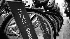 mobi in monochrome (Eric Flexyourhead) Tags: city urban canada detail bike bicycle vancouver zeiss downtown bc bokeh britishcolumbia repetition 169 mobi fragment shallowdepthoffield homerstreet 35mmf28 bicyclesharing bikesharing sonyalphaa7 zeisssonnartfe35mmf28za bw monochrome blackwhite
