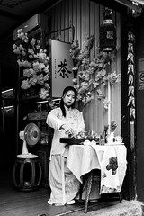 Tea time (Go-tea 郭天) Tags: chongqing républiquepopulairedechine tea ceremony ceremonial rules hanfu lady young woman alone lonely business house traditional tradition clothes history historical historic table cup pour pouring teapot pot tools fan flowers inside indoor beauty beautiful duty shop street urban city outside outdoor people candid bw bnw black white blackwhite blackandwhite monochrome naturallight natural light asia asian china chinese canon eos 100d 24mm prime portrait