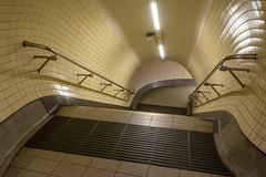 Stairwell in the underground (Jan van der Wolf) Tags: map196120v metro londen london staircase stairway stairs underground station handrails leuning lamp light depth
