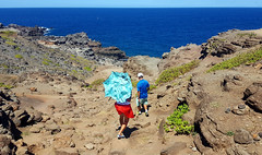 Malfunctioning Umbrella - Maui, Hawaii (TravelsWithDan) Tags: couple umbrella candid rocks mountains water ocean pacific island blue red maui hawaii usa streetphotography canong3x
