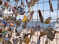 Love, actually (halifaxlight) Tags: canada princeedwardisland charlottetown harbour waterfront couple fence love sky sea padlocks locks