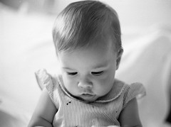 Wait while I check my messages... (Harald Philipp) Tags: child infant baby portrait bw agfa apx100 fm3a 135 35mm analog film aleksa