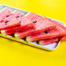 Triangular pieces of ripe red watermelon on a yellow background
