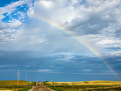 Gold at the end of the rainbow (darletts56) Tags: sky blue cloud clouds white grey gold golden green brown field fields pole poles power wire wires lines line highway gravel road roads rain rainbow thunder heavy bright farm farms prairie country countryside grass grasses saskatchewan canada stop sign post posts