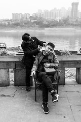 Maintenance (Go-tea 郭天) Tags: chongqing républiquepopulairedechine portrait saloon beauty men ear cleaning maintenance 2 together river side skyline water terrasse seat seated tools smoke smoking cigarette enjoy enjoying job specialist busy work working business care traditional tradition street urban city outside outdoor people candid bw bnw black white blackwhite blackandwhite monochrome naturallight natural light asia asian china chinese canon eos 100d 24mm prime bag purse