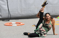 Come and Join Me! (Anthony Mark Images) Tags: stretching exercise warmups runningshoes blackleggings greendress hibiscusflowers hawaiian konagirl prettygirl funny hunourous smiling laughing streetperformer busker lovely pretty pavement waterloobuskercarnival waterloo ontario canada people portrait flyinhawaiian flickrclickx