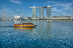 Tourist bum boat with Marina Bay Sands Hotel + Casino in Singapore (UweBKK (α 77 on )) Tags: singapore southeast asia sony alpha 77 slt dslr tourist bum boat marina bay sands hotel casino water reflection blue sky city urban ferris wheel art science museum shoppes shopping center mall shoppesbythebay marinabaysands ferriswheel singaporeflyer flyer architecture building