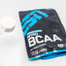 Hand holds little measuring spoon with ESN Nitro BCAA powder for athletes and a sporty lifestyle