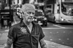 Punk Lives On (Leanne Boulton) Tags: urban street candid portrait portraiture streetphotography candidstreetphotography candidportrait streetportrait eyecontact candideyecontact streetlife man male face eyes expression mood emotion feeling punk hairstyle style tattoo piercing tone texture detail depthoffield bokeh naturallight outdoor light shade city scene human life living humanity society culture lifestyle people canon canon5dmkiii 70mm ef2470mmf28liiusm black white blackwhite bw mono blackandwhite monochrome glasgow scotland uk