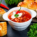 Traditional Ukrainian borscht with meat, vegetables and sour cream on a black background