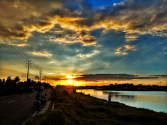 Opacarophile Pt. II (smzoha) Tags: sky bluesky cloud cloudy sunset dusk evening scattered vivid vibrant colors colorful river water ripple waves shore bank path poles wires beauty beautiful nature naturallights dyinglights twilight horizon bangladesh amazing mood shadows shade people streetphotography street
