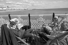 Lazy hazy days of summer (Finding Chris) Tags: besidethesea besidetheseaside canonuk deckchairs chrisbarbaraarps findingchris visualstorytelling canoneosr canonmirrorless canon24105 brightonpier holidaymakers daytrippers bw mono blackwhite
