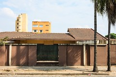 Se vende (zapota) Tags: orange yellow brown buildings architecture lines palmtree roof clouds