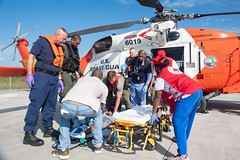 Sailors and Coast Guardsmen transport a patient in response to Hurricane Dorian in the Bahamas.