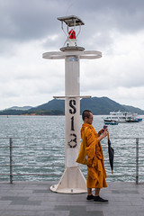 Down by the Sea, Hong Kong (Geraint Rowland Photography) Tags: sign sea pier portrait candid ocean somegreatstreetphotographydownbythewaterinhongkong wwwgeraintrowlandcouk monk calm people asianpeople asian streetportrait life canon wanderlustmagazine photographer