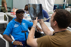 A Navy doctor embarked aboard USNS Comfort (T-AH 20) shows a patient an x-ray of arthritis in his knee.
