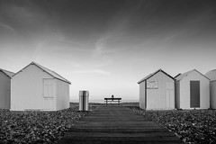 The boardwalk of Cayeux sur mer (jeffclouet) Tags: france europe nikon nikkor d850 nb pb bw bnw blackandwhite mono monochrome noiretblanc plage playa beach baie somme cayeux seaside seashore alone solo seul girl mer mar galets cabines banc bench banco picardie hut kid enfant