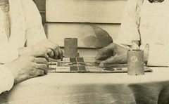 A Pair of Parcheesi-Playing Posers (Detail) (Alan Mays) Tags: men photos ephemera photographs postcards moustaches trickphotography mustaches foundphotos doubleexposures rppc trickphotos realphotopostcards old playing dice vintage ties glasses clothing boards funny humorous furniture antique humor games clothes cups shirts tables amusing players eyeglasses spectacles neckties boardgames bowties gamepieces photographicamusements vptp dicecups 1900s surprising parcheesi perplexing