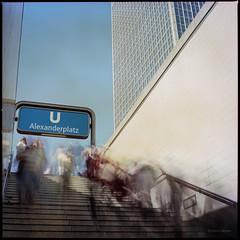 Alexanderplatz (Konrad Winkler) Tags: berlin alexanderplatz ubahnhof aufgang treppe hochhaus blauerhimmel menschen langzeitbelichtung heliopannd09 mittelformat kodakportra160 6x6 has epsonv800