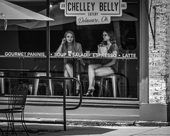 Window Seats (tim.perdue) Tags: black white bw monochrome nikon d5600 nikkor1680mm blackandwhite mono street candid girl woman person figure two window seat restaurant storefront sidewalk sign lunch eating seated couple pair duo belly eatery delaware ohio chelley gourmet paninis soup salad espresso latte