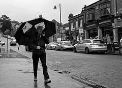 Dunlop Weather Protect. Sept 2019 (Simon W. Photography) Tags: rain wet weather umbrella street candid people streetphotography streetphoto streetphotographer photography streetstyle urban path person mature groupshot crowd sonyrx10iv sonyrx10m4 sonyuk sony sonydscrx10m4 blackandwhite blackwhite monochrome monotone greyscale grayscale bw bnw nocolour nocolor lightandshadow