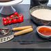 Kochutensilien für die italienische Küche: Pizzamesser, Pizzaschneider, Tomatensauce und roher Pizzateig auf einem grauen Tisch