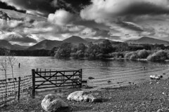Storm clouds over Derwentwater (Iand49) Tags: derwentwater lake water keswick cumbria lakedistrict england europe causeypike fells mountains ruggedscenery beach fence gate boulders trees woodland shingle november autumn stormclouds cloudy darksky brooding monochrome blackandwhite outdoors nature dramatic landscape majesticscenery tourism fellwalking rambling hiking countryside crags holidays travel rural