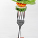 Woman holding a fork with fresh vegetables. Healthy eating concept