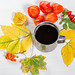 Iron mug with coffee surrounded by autumn berries and leaves