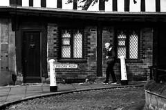 Street (lightersideofdark) Tags: blackwhite street streetphotography dark outside outdoors brickwall brick wall architecture urban person tudor old bollards windows door cobbles