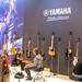 Yamaha Instrumentenvorstellung: Besucher spielen auf Akkustik-Gitarren und Bassgitarren
