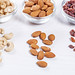 Cashews, almonds and raisins in glass bowls and scattered on a white wooden background
