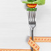 Fork with slices fresh tomato, cucumber, lettuce and measuring tape. The concept care of the figure