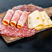 Sliced salami, ham, and cheese on an old kitchen wooden Board on a black background