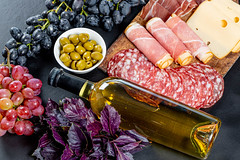 Full bottle of white wine with traditional snack on black background. Top view (wuestenigel) Tags: sausage fillet cut slice roll portion background meat red salami olives ham cooked kitchenboard ripe wine cheese bottle basil piece cooking bacon food leaves blue grapes fruit pork pickled purple preparation freshness black green fresh sliced uncooked white 2019 2020 2021 2022 2023 2024 2025 2026 2027