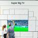 Menschen stehen vor dem Super Big TV QLED 75