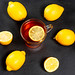 Glass Cup with black tea surrounded by fresh ripe lemons on a black background