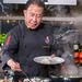 Chef Martin Yan cooks crab chips in a pan during a German live cooking show