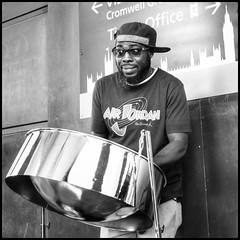 Steel Drum (NickD71) Tags: panasonic lumix dmc lx100 mk1 compact camera advanced snapseed mono monochrome street people daily life candid london england united kingdom uk steel drum busker caribbean calypso sounds music cool entertainment wide eyed shades westminster tube station