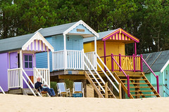Life's a beach hut (2) (Photography And All That) Tags: life blue trees summer man colour beach yellow coast newspaper seaside sand chair sitting glare colours chairs steps huts hut lilac coastal scowl beaches daytime times sands seated glaring scowling wood wooden balcony sony balconies leisure whitsend sonyalpha sonyilce7m3 sonyalpha7mark3 norfolk wells wellsnextthesea