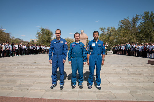 The backup crewmembers for the next launch to the space station in front of a statue of Sergei Korolev