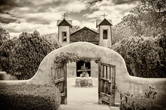 The pilgrimage site of El Santuario de Chimayo, a National Historic Landmark in Chimayo, New Mexico (diana_robinson) Tags: elsantuariodechimayo chimayo church romancatholicchurch clouds landscape highroadtotaosscenicbyway sangredecristomountains newmexico highdesert mountains sanctury nationalhistoriclandmark pilgrimagesite adobe carvedwoodendoors entranceway blackandwhite sepia