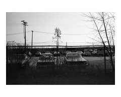 Cars parked in a fenced area (Richard C. Johnson: AKA fishwrapcomix) Tags: leicam2 leitzsummaron35mmf28 film ilfordxp1 analog analogue scanfromnegative filmisnotdead iusedtoshootfilm istillshootfilm blackandwhite bw monochrome trees autumn fence automobiles utilitypoles barberedwire powerstation 1980s archive mybackpages iwassomucholderthan industry building ilfordxp2 economicdecline ronaldreagantrickledowndespair