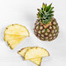 Half and pieces of fresh pineapple on white background
